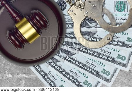 50 Us Dollars Bills And Judge Hammer With Police Handcuffs On Court Desk. Concept Of Judicial Trial