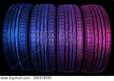 Studio Shot Of A Set Of Summer Car Tires In Pink And Blue Tones. Tire Stack Background. Car Tyre Pro