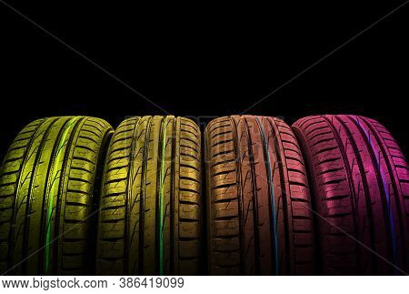 Studio Shot Of A Set Of Summer Car Tires In Yellow And Pink Tones. Tire Stack Background. Car Tyre P