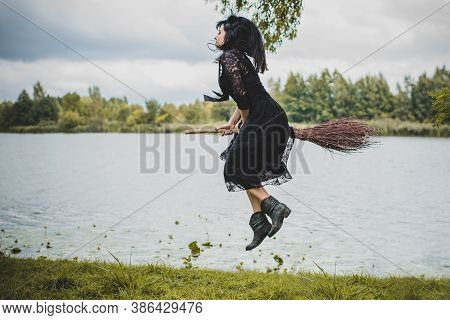 Young Beautiful And Mysterious Witch Woman Flying On The Broom In Woods. Levitation, A Witch In A Ha