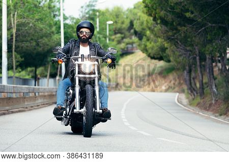 Biker With Helmet, Sunglasses And Leather Jacket Riding His Motorcycle On The Road, Concept Of Freed
