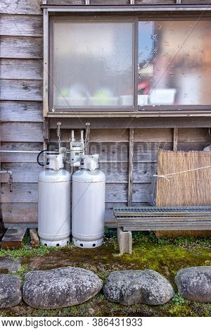 Gas Bottles Standing Outside Wall Near Window Of House For Heating And Cooking