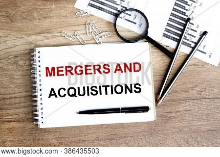 Mergers And Acquisitions. Text On Wood Background On White Sheet Of Paper