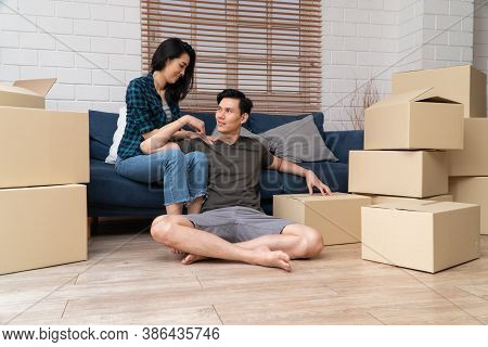 Happy Young Asian Couple Sitting On The Sofa For Rest After Moving To A New House On The First Day.
