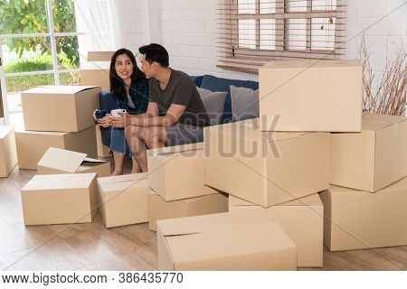 Happy Young Asian Couple Holding A Coffee Cup And Sitting On The Sofa For Rest After Moving To A New