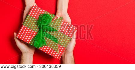 Top View Of Holding A Gift In Female And Male Hands On Colorful Background. Woman And Man Give And R