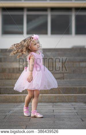 Little Girl In Pink Dress Spinning Around And Dancing On The Street