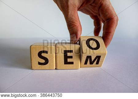 Seo Versus Sem. Male Hand Turns A Cube And Changes The Expression 'seo' To 'sem' Or Vice Versa. Conc
