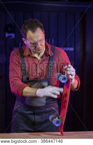 Middle-aged Man In Jumpsuit Testing Weels Of Plastic Kids Skateboard In Home Workshop. Reliability T