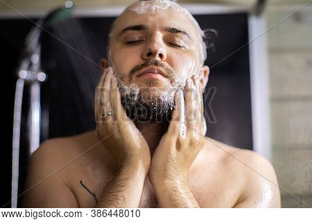 Close Up View Of Handsome Man With Closed Eyes Washing Beard In Bathroom, Taking Shower. Lifestyle,