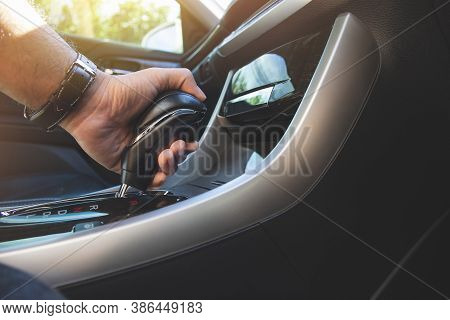 The Driver's Hand Holds The Gear Lever Of The Automatic Transmission In The Car