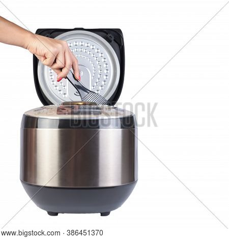 Girl With A Spoon Stir Food In A Multicooker Close Up. Isolated On White Background. A Female Hand H