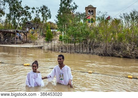 QASR El-YAHUD, ISRAEL - MARCH 2, 2020: Baptism of children. The place of baptism of Jesus Christ on Jordan River. The man in white shirts stand in  water and hold the child.