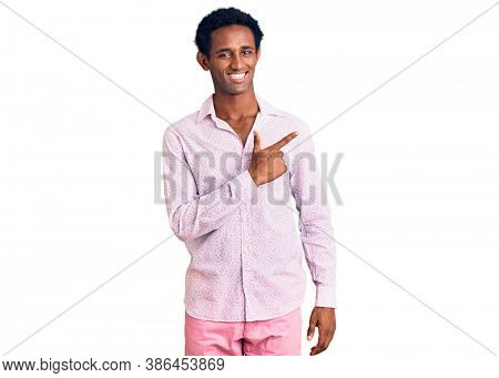 African handsome man wearing casual pink shirt cheerful with a smile of face pointing with hand and finger up to the side with happy and natural expression on face