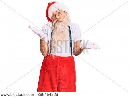 Old senior man with grey hair and long beard wearing santa claus costume with suspenders clueless and confused expression with arms and hands raised. doubt concept.