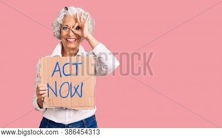 Senior grey-haired woman holding act now banner smiling happy doing ok sign with hand on eye looking through fingers