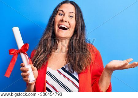 Young beautiful brunette smart woman holding graduated degree diploma over blue background celebrating achievement with happy smile and winner expression with raised hand