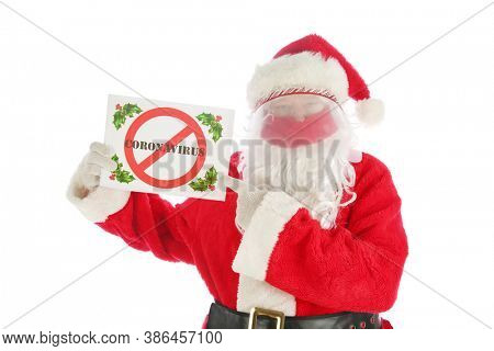 Coronavirus Santa Claus. Santa wears a Face Shield, Velvet Face Mask and holds a NO CORONAVIRUS sign. Isolated on white. Coronavirus has created a world wide Pandemic.