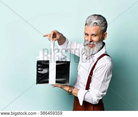 Bearded Elderly Man In A White Shirt, Brown Pants And Suspenders, A Bracelet. He Wants To Open A Sil