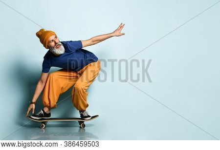 Gray-haired Man In Years In A T-shirt, Orange Pants And A Hat, Sneakers, Bracelets. Crouching, Ridin
