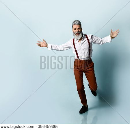 Bearded Old Man In A White Shirt, Brown Trousers With Suspenders And Black Loafers. He Threw Up His
