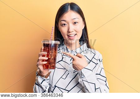 Young beautiful chinese woman drinking cola refreshment beverage smiling happy pointing with hand and finger