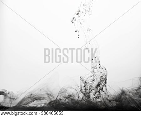 Closeup Of A Black Ink In Water In Motion Isolated On White. Ink Swirling Underwater. Colored Abstra