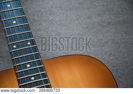 Close-up Guitar Fretboard With Strings Isolated On A Blurred Gray Background With Copy Space. Music
