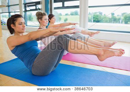 Women doing boat pose in yoga class in fitness studio