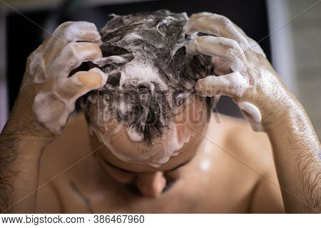 Young Bearded Naked Brunette Man Massaging His Head In Shower With Shampoo Foam Or Hair Care Product