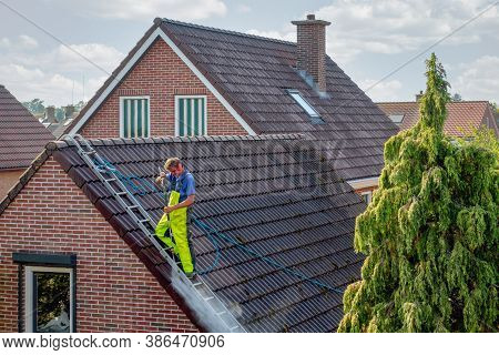 Urk, The Netherlands - September 15, 2020: Cleaner With Pressure Washer At Roof Of House Cleaning Th