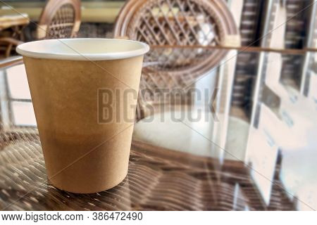 Close Up Craft Cardboard Cup With Coffee On Glass And Straw Table. Wooden Chairs, Interior Of A Smal