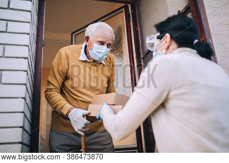 Young Female Volunteer In Mask Gives An Elderly Man Boxes With Food Near His House. Quarantined, Iso