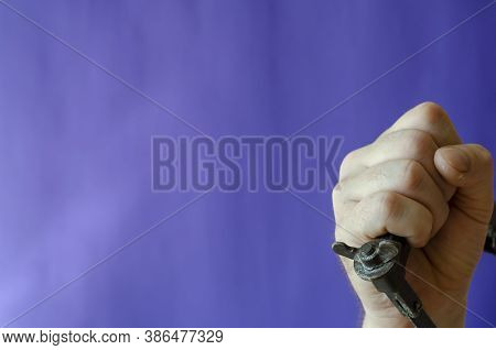 Old Hacksaw For Metal In Hand On A Blue Background. The Male Hand Firmly Holds The Hand-held Metal C