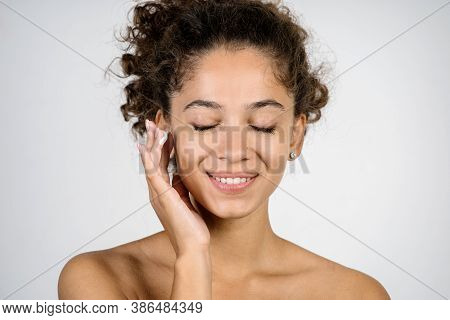 Skincare Concept. Portrait Of Nude Happy Young African American Woman Applying Moisturizing Face Lif