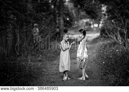 little friends excitedly talking standing in the Park. Black and white photography.