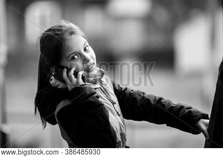 Little girl talking on phone in the street. Black and white photography.