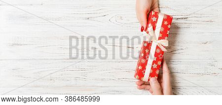 Top View Of Giving And Receiving A Gift On Wooden Background. Present In Male And Female Hands. Love