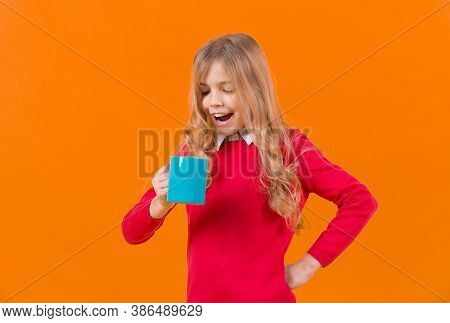 Tea Or Coffee Break. Girl With Long Blond Hair In Red Sweater Hold Mug. Child Smile With Blue Cup On