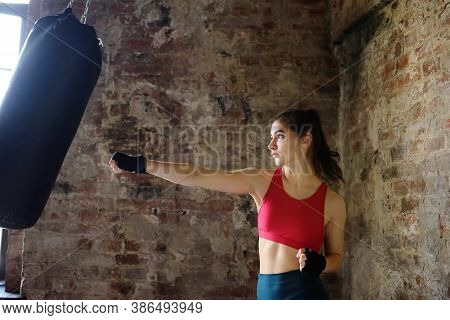 Young Woman Hits Punching Bag During A Boxing Training. Female Boxer Doing Fitness. Regular Sports B