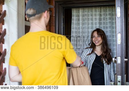 Delivery Man In Yellow T-shirt Handing Paper Bags To Happy Recipient, Beautiful Woman Customer Recei