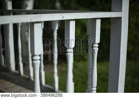 Balusters In The Decoration Of The Veranda Railings. An Architectural Element Made Of Wood. An Old M