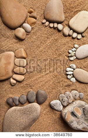 trace feet family of a pebble stone on the sea sand backdrop