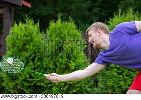 Badminton Player With Racket In Action. Young Handsome Guy Playing Badminton Outdoors In Park, Green