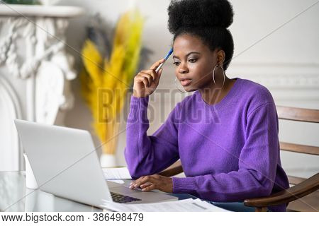 Afro-american Millennial Student Woman With Afro Hairstyle Browsing Information On Laptop, Preparing