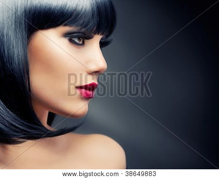 Beautiful Brunette Woman Portrait over Dark Background. Healthy Black Hair
