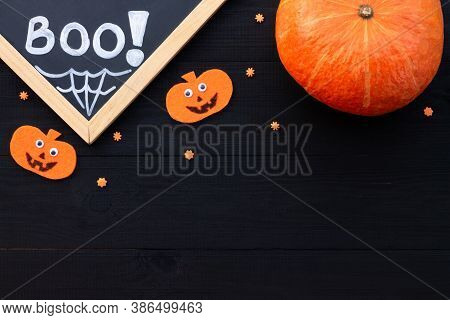 Orange And Black Halloween Flatlay. Chalk Inscription Boo, Pumpkins From Felt On A Black Wooden Back