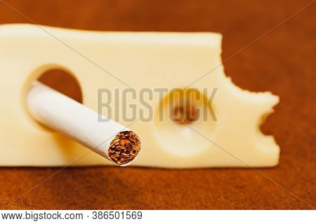 Close Up Cigarette In The Hole Of A Piece Of Cheese, Quit Smoking, Stop Smoking Cigarette Concept.