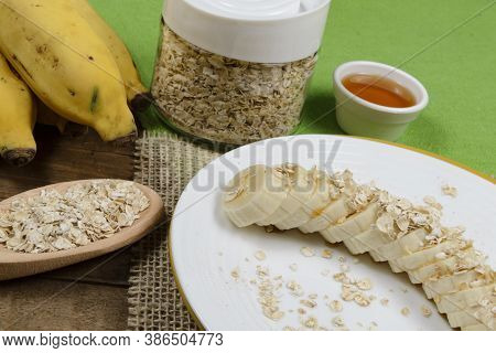 Plate With Sliced Banana, Oatmeal In Spoon And Jar Of Honey