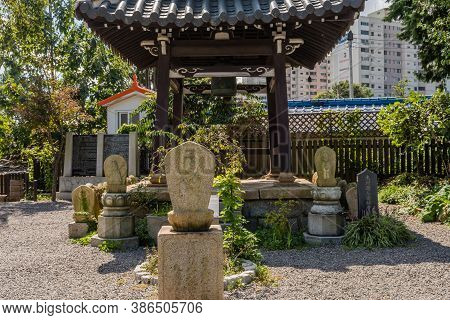 Geumsan, South Korea; September 12, 2020: Reliefs Of Monk Carved In Rocks Surround Wooden Bell Pavil